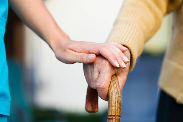 Care provider holding senior patient's hand