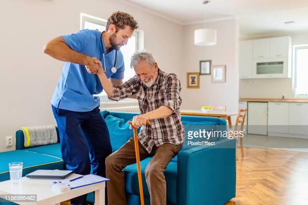 travailleur de soin aidant l'homme aîné pour se lever - aide soignante photos et images de collection
