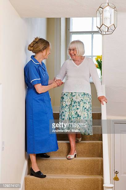 care worker helps a senior woman down the stairs