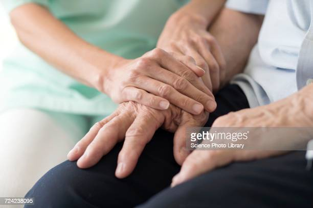 care worker holding senior mans hands - social services stock pictures, royalty-free photos & images
