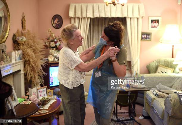 Care worker Sarah Cox visits client Patricia Taylor at her home during the coronavirus pandemic on May 08, 2020 in Borehamwood, England. They have a...