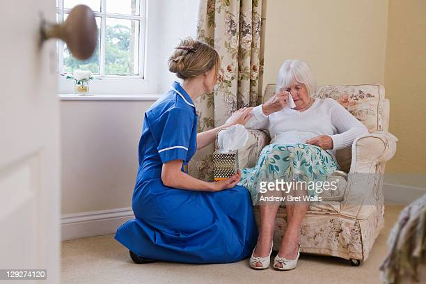 Care worker supports a grieving elderly woman