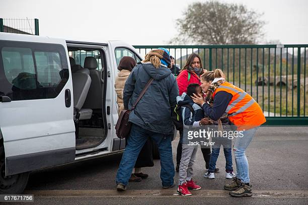 Care workers bring child migrants to a reception point outside the Jungle migrant camp before boarding buses to refugee centres around France on...