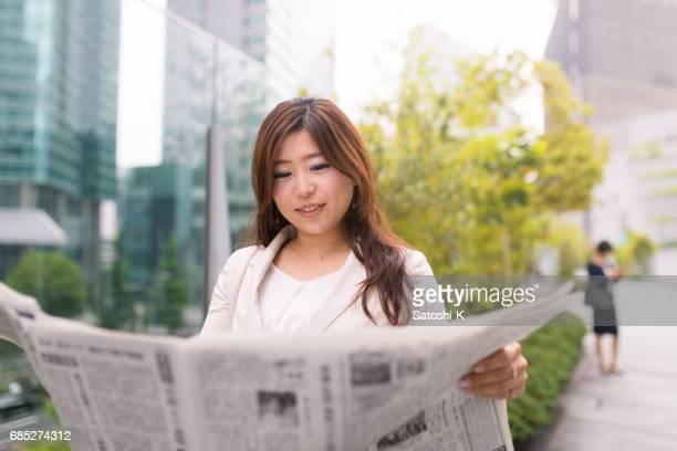 キャリア ・ ウーマン市で新聞を読む