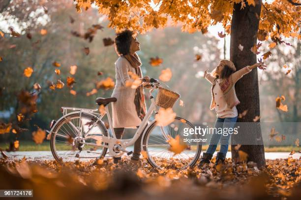 carefree african american mother and daughter enjoying among autumn leaves at the park. - autumn falls stock pictures, royalty-free photos & images