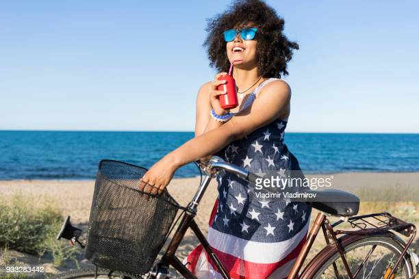 carefree african woman drinking cocktail on beach - american flag ocean stock pictures, royalty-free photos & images