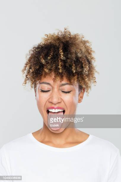 carefree afro american woman sticking out tongue - sticking out tongue stock pictures, royalty-free photos & images