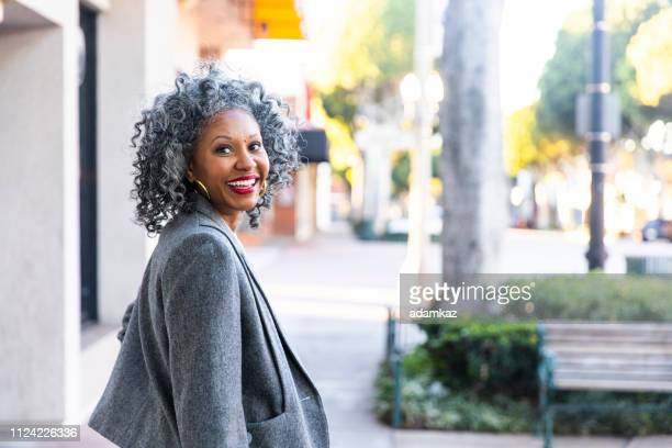 a carefree black woman looking back over her shoulder - adulto in età matura foto e immagini stock