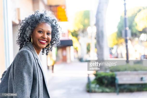 une insouciance noir femme à la recherche revient sur son épaule - cheveux gris photos et images de collection