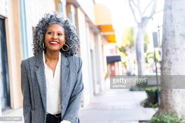 um despreocupado preto mulher olhando sobre o ombro dela - adulto de idade mediana - fotografias e filmes do acervo