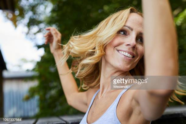 carefree blond woman outdoors - human arm stock-fotos und bilder