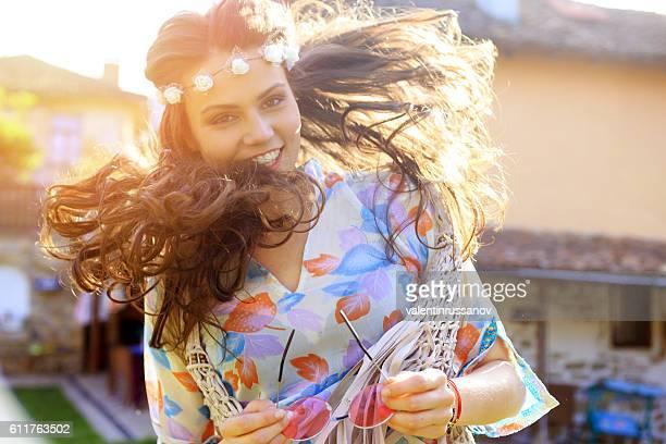 Carefree boho woman dancing on grass