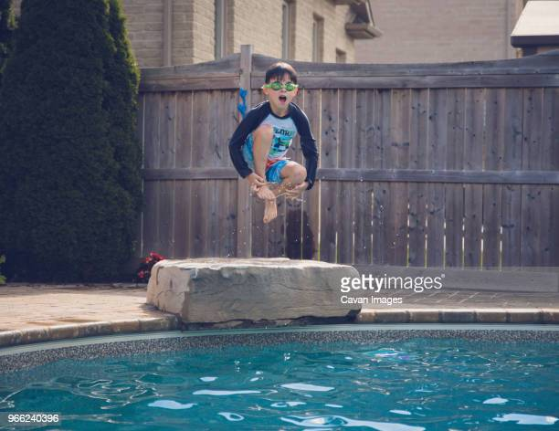 carefree boy jumping into swimming pool against fence - swimming goggles stock pictures, royalty-free photos & images