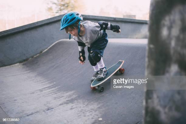 carefree boy skateboarding on sports ramp at skateboard park - caneleira roupa desportiva de proteção imagens e fotografias de stock
