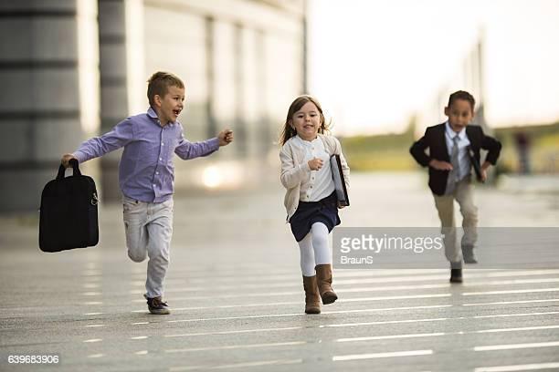 Carefree business kids having fun while running outdoors.