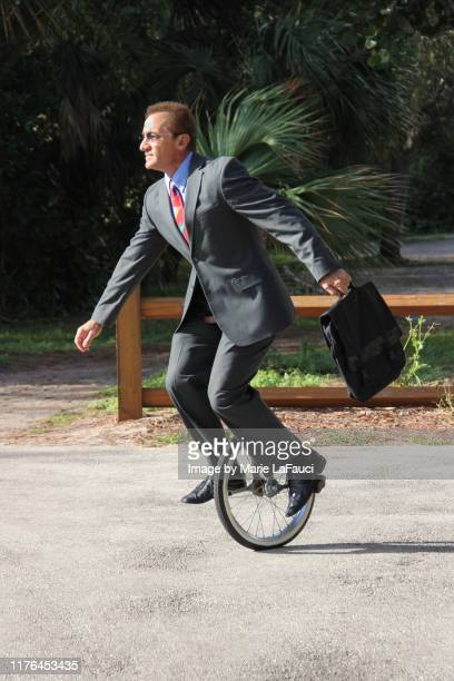 carefree businessman riding a unicycle to work - fauci stock pictures, royalty-free photos & images