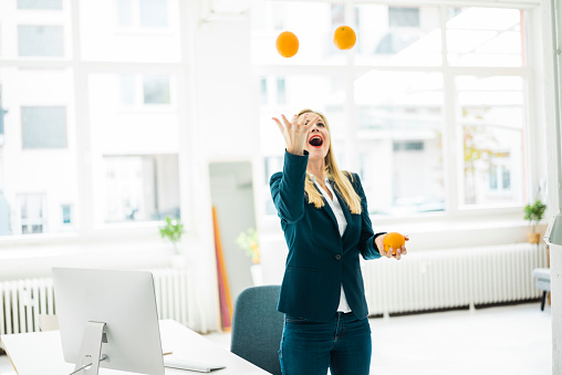 Carefree businesswoman juggling with oranges in office - gettyimageskorea