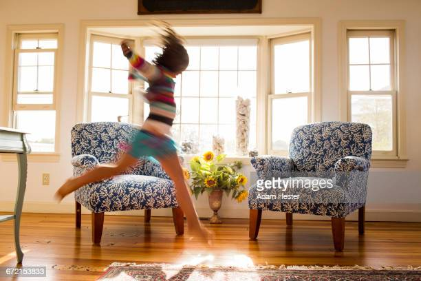 Carefree Caucasian girl running and jumping in livingroom