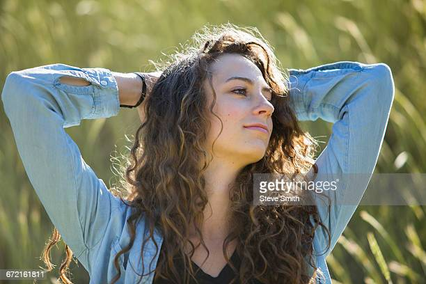 Carefree Caucasian woman with hands behind head in field of tall grass