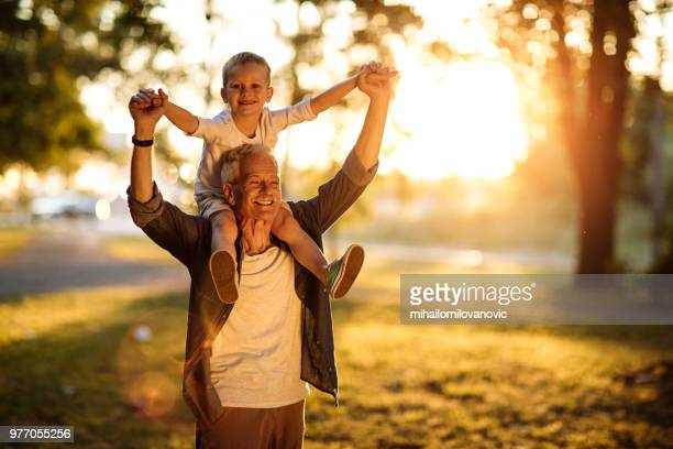 carefree child and a happy grandpa - grandfather stock pictures, royalty-free photos & images