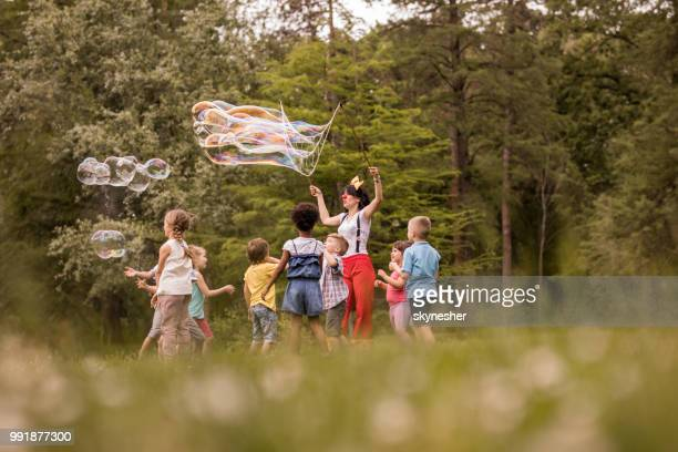 carefree children playing with rainbow bubbles made by artist in the park. - street artist stock pictures, royalty-free photos & images