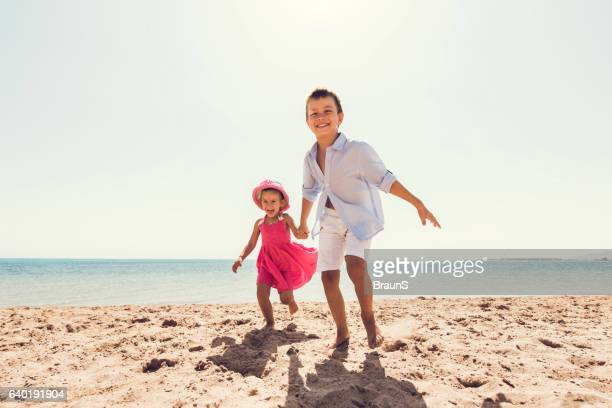 Carefree children running together on the beach.