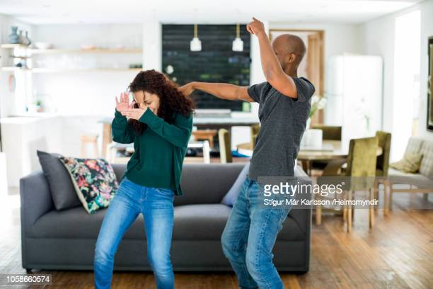 carefree couple dancing in living room at home - gesturing stock pictures, royalty-free photos & images