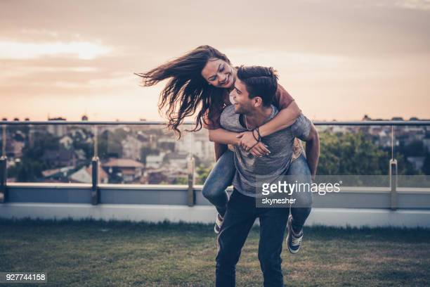 carefree couple having fun while piggybacking on a penthouse balcony. - piggyback stock photos and pictures