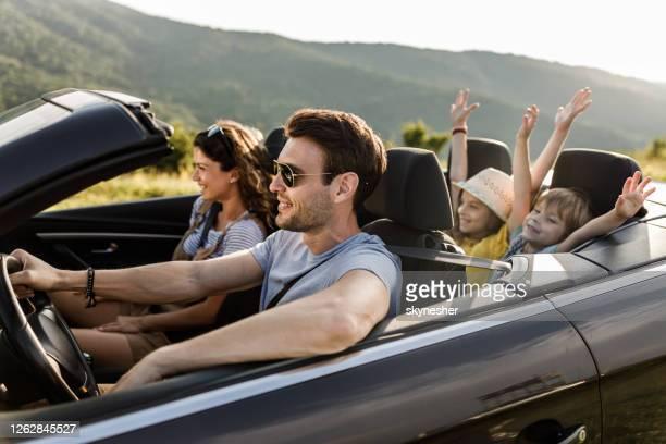 コンバーチブルカーでロードトリップ中に楽しんで気楽な家族。 - ドライブ旅行 ストックフォトと画像