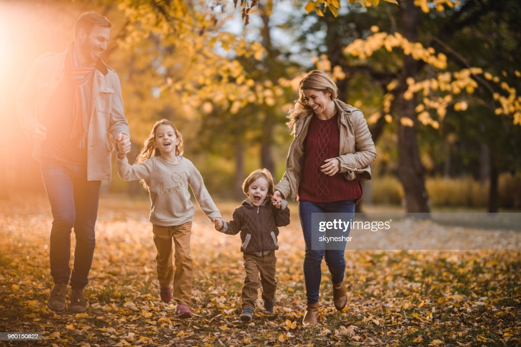 Unbeschwerte Familie Spaß beim Händchenhalten und Herbsttag einfahren. : Stock-Foto