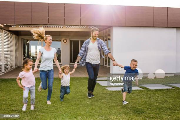 carefree family holding hands and running in front of their house. - penthouse girls stock pictures, royalty-free photos & images