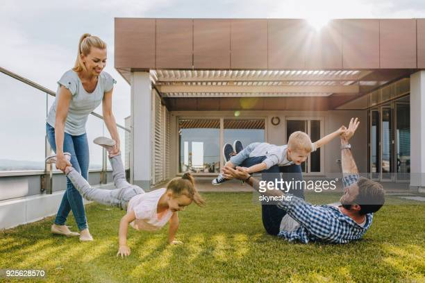 carefree family playing on grass in front of their penthouse. - penthouse girls stock pictures, royalty-free photos & images