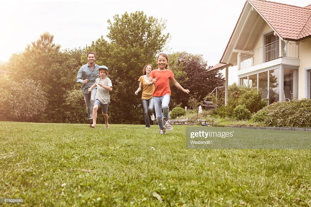 Carefree family running in garden : Stock Photo