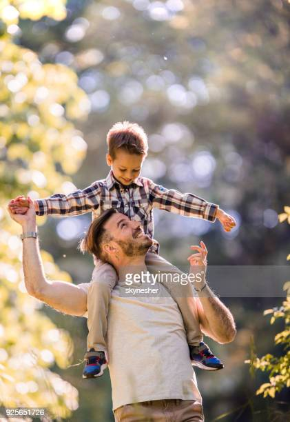 carefree father having fun while carrying his small son on shoulders in nature. - carrying a person on shoulders stock photos and pictures