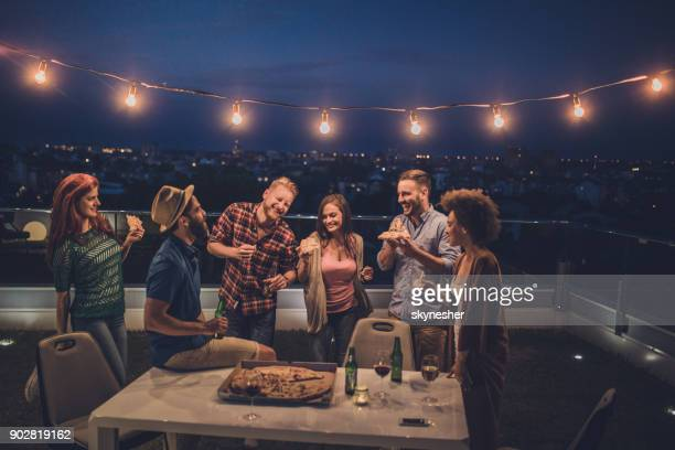 carefree friends having fun on a night party at penthouse terrace. - outdoor party stock pictures, royalty-free photos & images