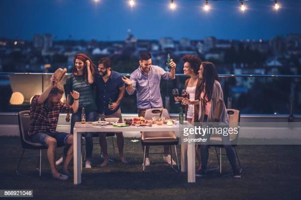 Amis sans soucis s'amuser sur une fête au balcon de l'appartement.