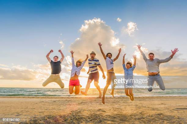 Carefree friends jumping for joy on cloudy beach