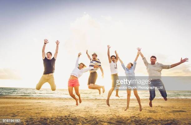 Carefree friends jumping for joy on sunny beach