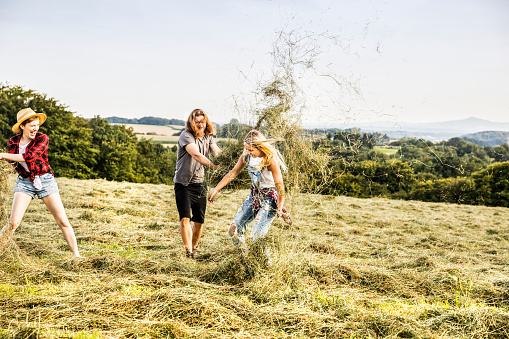 Carefree friends playing with hay in a field - gettyimageskorea