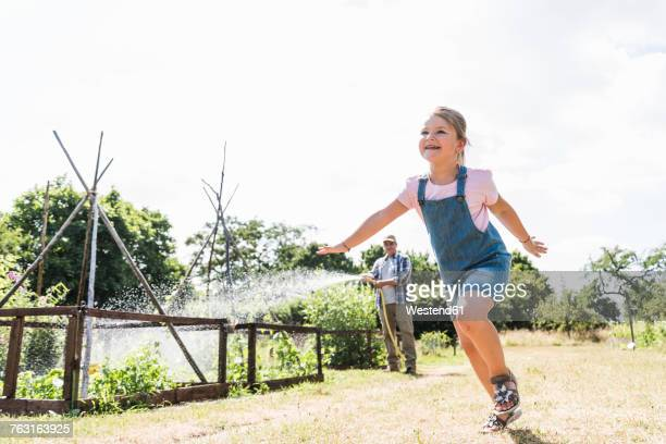Carefree girl in garden with grandfather watering plants