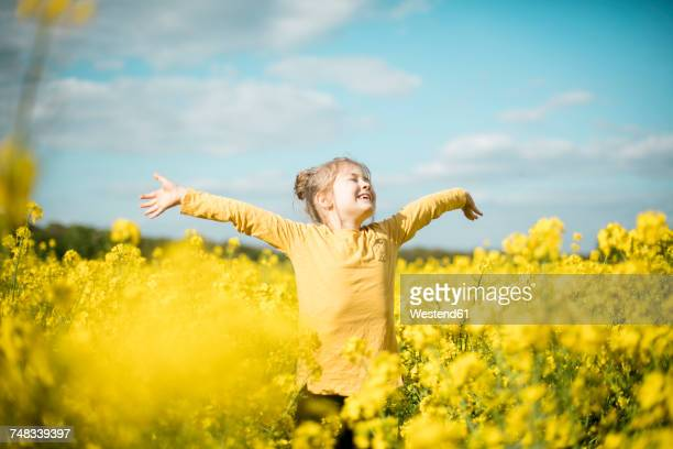 carefree girl in rape field - printemps photos et images de collection