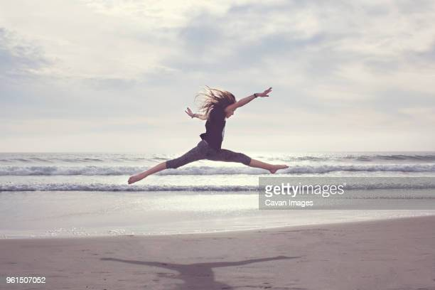 carefree girl jumping at beach against cloudy sky - benen gespreid stockfoto's en -beelden
