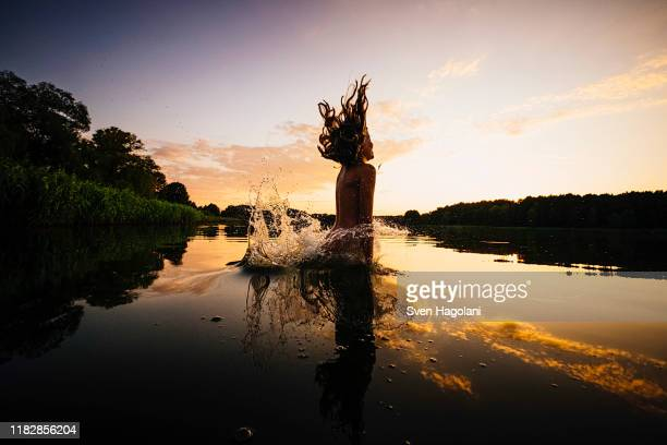 carefree girl jumping into lake at sunset, barnin, mecklenburg-vorpommern, germany - travel stock-fotos und bilder