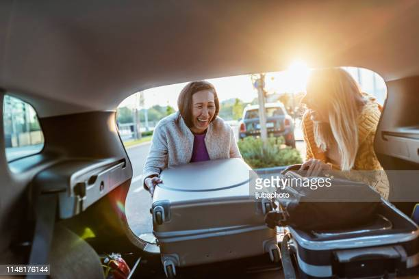 carefree girlfriends enjoying car trip - packing stock pictures, royalty-free photos & images