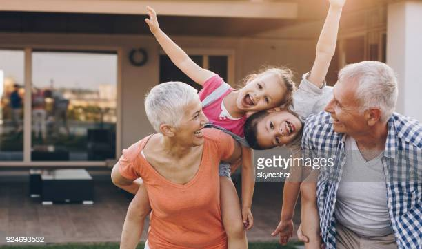 carefree grandparents piggybacking their joyful grandkids in the front yard. - multigenerational family stock photos and pictures
