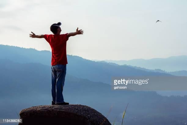 ' hombre feliz sin preocupaciones disfrutando de la libertad de la naturaleza en la cima de una montaña, con un acercamiento de águila - flanco de valle fotografías e imágenes de stock