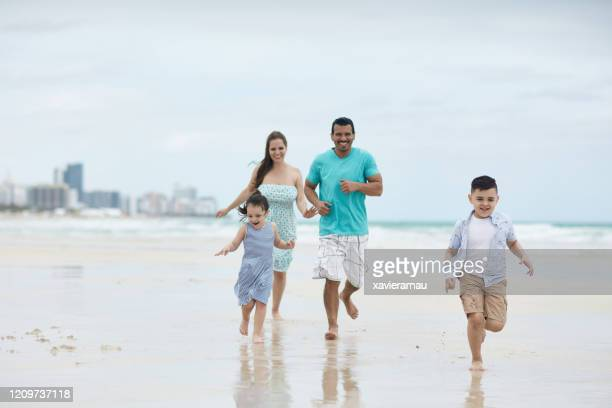 carefree hispanic family running along miami beach shoreline - gulf coast states stock pictures, royalty-free photos & images