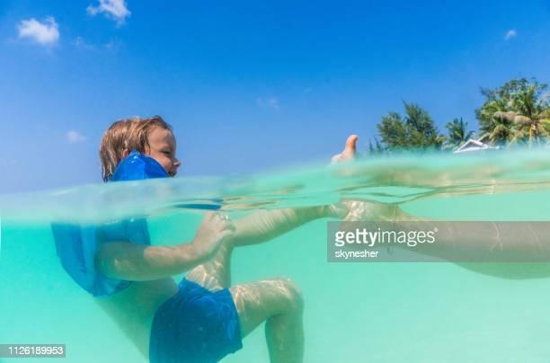enfant sans soucis avec des ailes de l'eau s'amuser avec sa mère dans la mer. - membre partie du corps photos et images de collection