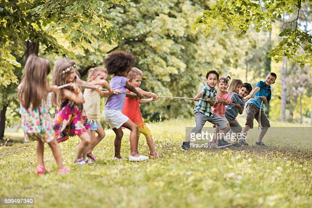 Carefree kids having fun while playing tug-of-war in nature.