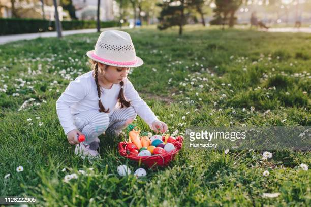 carefree little girl playing with basket full of easter eggs - easter egg hunt stock photos and pictures